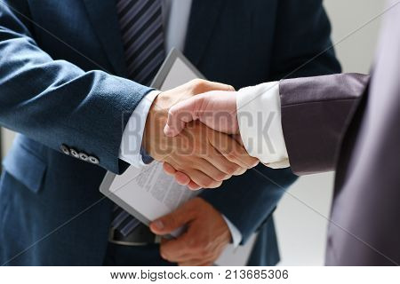 Man in suit shake hand as hello in office closeup. Friend welcome mediation offer positive introduction greet or thanks gesture summit participate approval background strike arm bargain concept