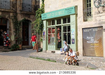Pezenas, Herault, France - Aug 26 2017: Sunny Traditional Cobbled Street Scene In The Languedoc Town