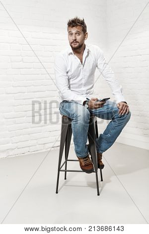 Full length indoor portrait of handsome man in casual cloth sitting on barstool using smart phone.