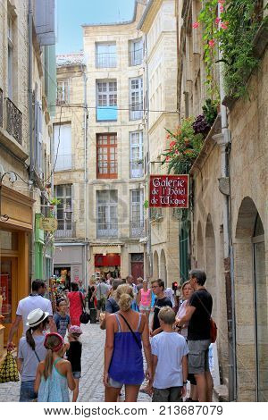 Pezenas, Herault, France - Aug 26 2017: Busy Narrow Traditional Street Of Stone Buildings, Full Of T
