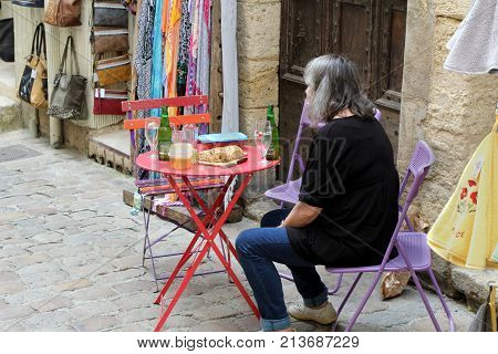 Pezenas, Herault, France - Aug 26 2017: Older Woman Sitting Down At An Outside Table To Enjoy Lunch