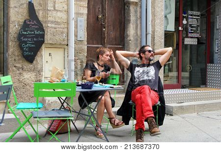 Pezenas, Herault, France - Aug 26 2017: Man And Woman Hipster Couple Relaxing At A Street Cafe Table