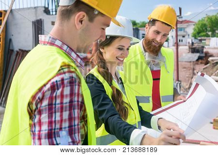 Young and confident female architect smiling while sharing ideas about the plan of a building under construction outdoors with two blue-collar workers