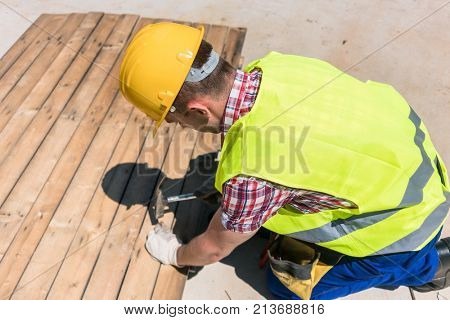 High-angle view of a blue-collar worker wearing yellow hard hat, safety vest and gloves while using a hammer during work on the construction site
