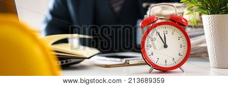 Red alarm clock shows late time closeup and tired office male clerk in suit take nap on table workplace full of exam papers. Career frustration freelance employment fail study problem low energy down