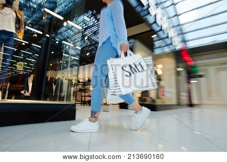 Hurrying shopper with paperbags walking along window-display in large mall during sale