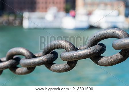 Five Links in Iron Chain hanging in front of water