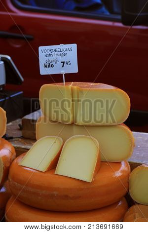 Traditional Dutch cheeses on display on a market stall. Text on tag in Dutch: Special offer cheese extra old and spicy one kilo for