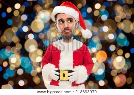christmas, holidays and people concept - sad man in santa claus costume over lights background (funny cartoon style character with big head)