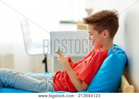 childhood, technology and communication concept - happy smiling boy with smartphone at home