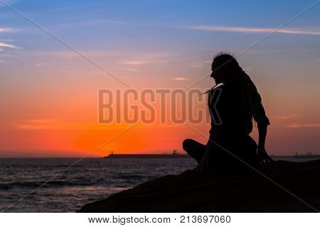 Silhouette yoga woman with dreadlocks on the banks of the sea during twilight.