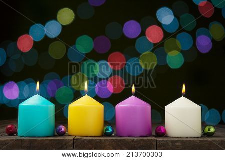 Multicolored burning candles with bokeh on black background.Concept of New Year and Xmas