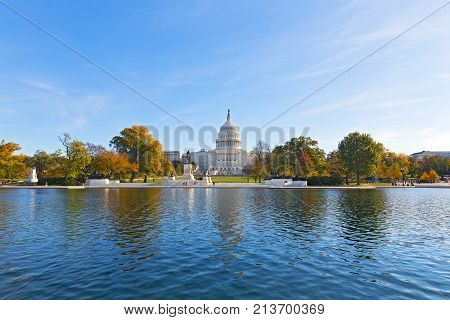 Capitol Hill panorama with reflection pool in late autumn Washington DC USA. US Capitol in fall on a cold sunny morning with colorful deciduous trees in its front.