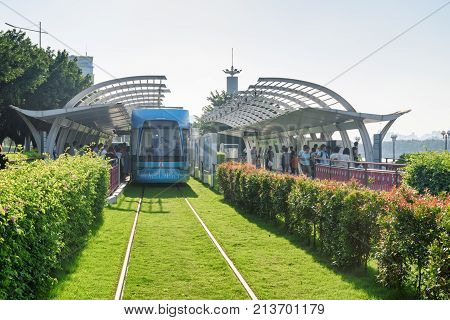 Guangzhou China - September 16 2017: Boarding to a blue tram. System of Guangzhou Trams is popular among tourists. The tram line connecting the Canton Tower and Wanshengwei along the Pearl River.