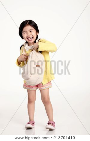 Studio portrait of a happy asian girl holding a bag