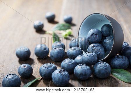 Blueberries closeup with green leaves on rustic wooden table.Concept healthy eating
