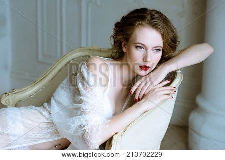 Fashionable female portrait of cute lady in white robe indoors. Close up beautiful sexy model girl in elegant pose. Closeup beauty brunette woman with hairstyle and makeup. Glamorous face with make up
