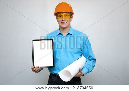 Engineer award mockup. Best worker certificate. Builder in a hardhat holding in one hand empty photo frame and project documentations by another hand. Project documentation. Grateful letter.