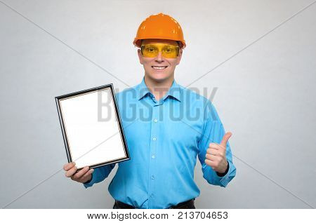Engineer award mockup. Best worker certificate. Builder in a hardhat holding in one hand blank photo frame and showing thumbs up gesture sign by another hand. Project documentation. Grateful letter.