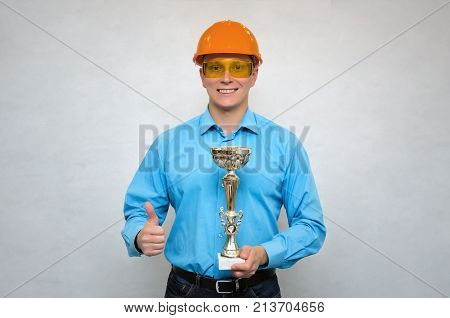 Builder award. Best construction worker. Builder in a hardhat holding in one hand gold cup award trophy and showing thumbs up gesture sign by another hand. Worker of the year.