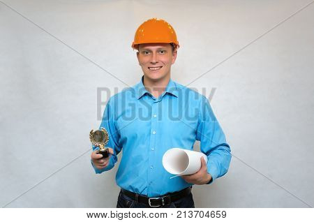 Builder award. Best construction worker. Contractor Winner. Builder in a hardhat holding in one hand gold medal award trophy and project documentation in another hand.