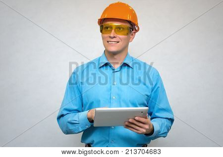 Happy builder worker in a hardhat using a tablet computer in his hands smiles and looks up isolated. Engineer learning construction plans.