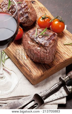Grilled fillet steaks on cutting board and glass of red wine