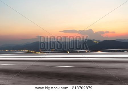 blurry emtpy asphalt road by green mountains in colorful cloud sky at dawn