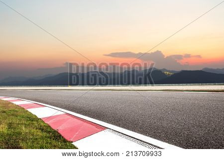 emtpy asphalt road by green mountains in colorful cloud sky at dawn