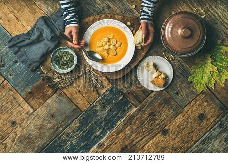Flat-lay of female hands and Fall warming pumpkin cream soup palte with croutons and seeds over rustic wooden table background, top view. Autumn vegetarian, vegan, healthy comfort food eating concept.