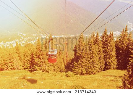 A Toned Picture Of Bright Red Cableway Cabin Moving To The Top Of The Mountain Over The Beautiful La
