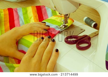 Sewing Process the sewing machine sew women's hands. sewing machine and female scissors. Woman's Hand Sewing Quilt - Retro color