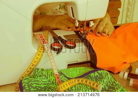 processes of sewing on the sewing machine sew women's hands sewing machine. Female tailor threading leather material on sewing machine. designer making a garment in her workplace - Retro color