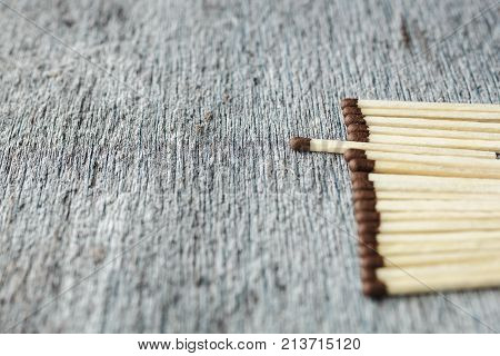 a row of matches against a gray background, one match is pushed forward. Copy space