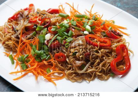 Asian instant noodles with bean sprouts, green onion, carrot and pepper
