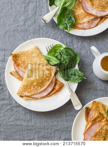 Crepes with ham and spinach. Delicious nourish breakfast or snack on a grey background top view