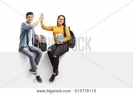 Teenage students seated on a panel high-fiving each other and looking at the camera isolated on white background