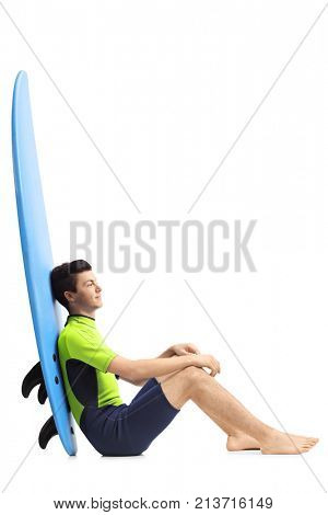 Teenage surfer sitting on the floor and leaning on a surfboard isolated on white background