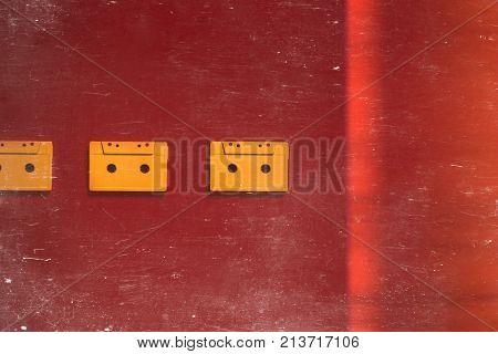 Yellow Audio Cassettes Tapes On Red Background, Top View Toned And Scratches. Creative Concept Of Retro Technology