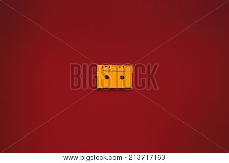 Yellow Audio Cassette In Center Tapes On Red Background, Top View. Creative Concept Of Retro Technology