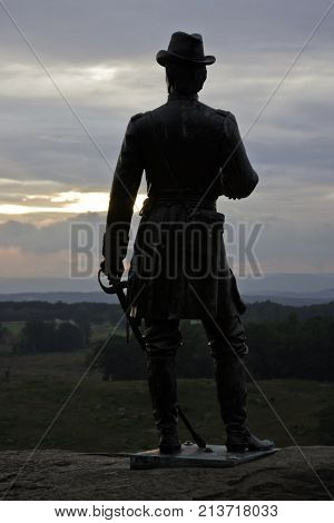 Gettysburg, Pennsylvania - September 9, 2009 - Vertical of a slightly silhouetted statue of a Civil War Officer with saber in hand overlooking the battlefields of Gettysburg Military Park, Pennsylvania a little before sunset on a cloudy day in September.