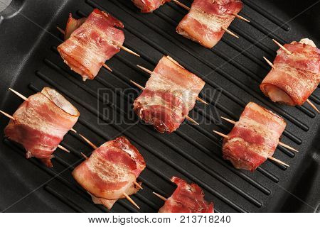 Bacon wrapped chicken nuggets on grill pan, closeup