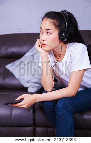 Young Woman Listening To Music In Headphones With Moblie On Sofa At Home