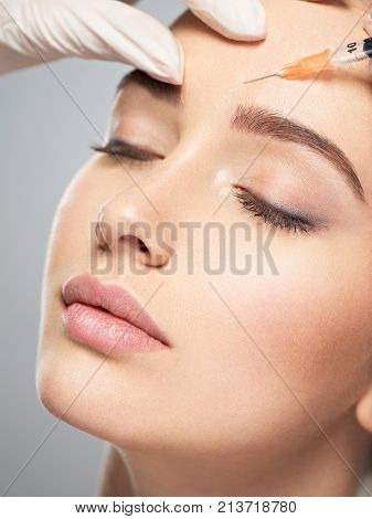 Woman getting cosmetic injection of botox near eyes, closup. Woman in beauty salon. plastic surgery clinic.