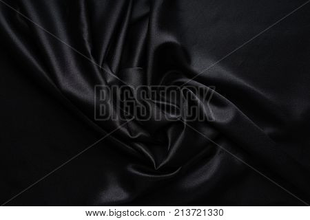 Dark black silky, satin fabric, wave, draperies. Beautiful textile backdrop to create creative layouts for black Friday. Close-up. Top view