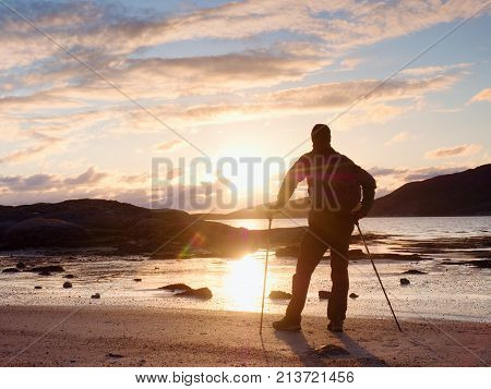 Walker Watch Sunny Spring Daybreak Over Sea. Hiker With Backpack Stand On Sandy Shore. Sun Rays