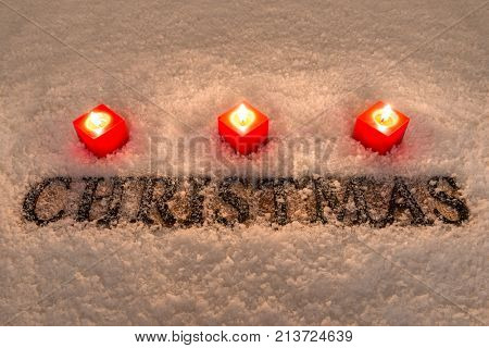 The word Christmas in wooden letters on a snow background illuminated by three red candles.