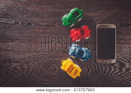Four cars model and phone on wooden background with copyspace. concept of car rental, auto car insurance and travelling