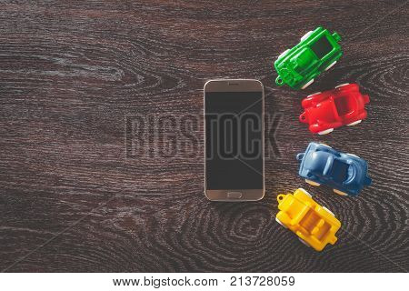 Four cars model and smarphone on wooden background with copyspace. concept of car rental, auto car insurance and travelling