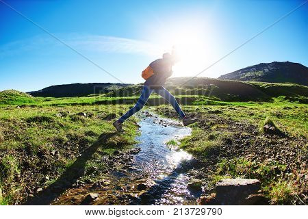 woman traveler with small orange backpack on a walk in the Valley of the river of Hveragerdi Iceland. Hiking Tour of Reykjadalur Hot Springs. woman jumping over creek